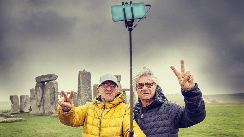 Dos hombres maduros, posando y tomando un selfie en el sitio arqueológico de Stonehenge, Reino Unido.