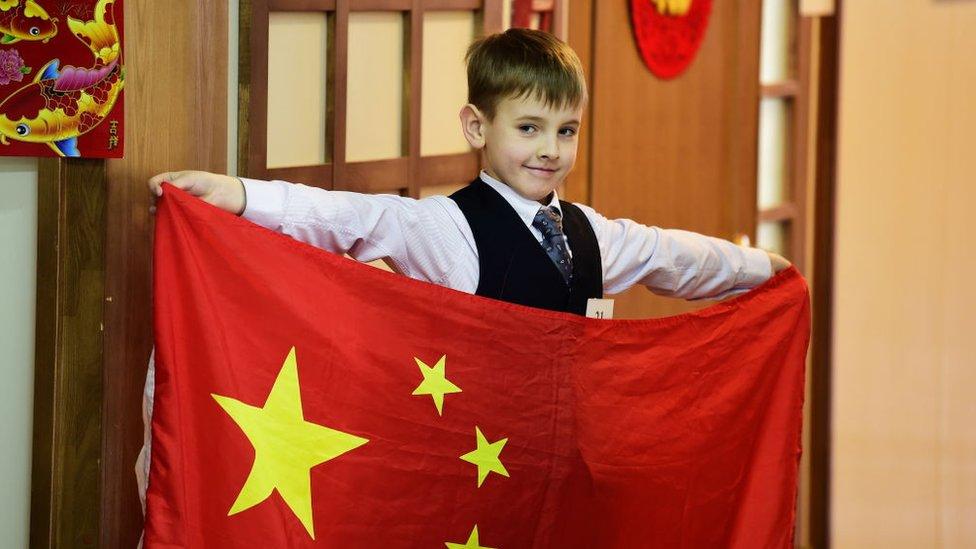 Un niño ruso sostiene una bandera nacional china durante la final en un Instituto Confucio.