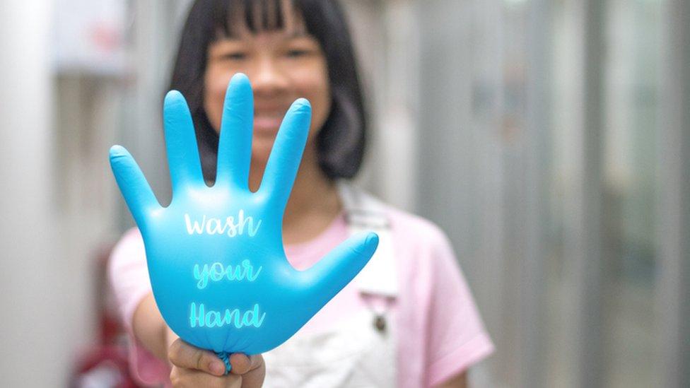 """Una mujer sostiene un guante con la frase """"lávate las manos"""" en inglés."""