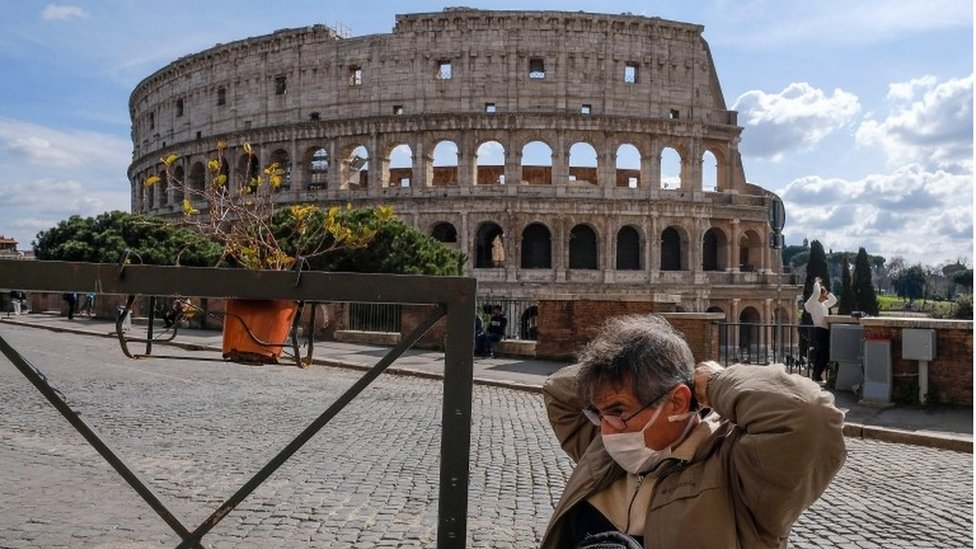 A tourist wearing a mask sits at the tables of a restaurant in front of the Colosseum, in Rome, Italy, 9 March 2020.