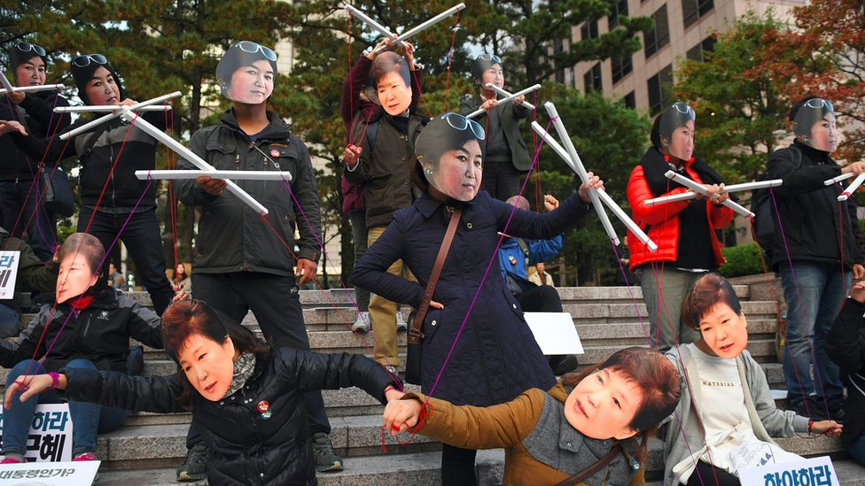 Protesters wearing masks of South Korean President Park Geun-hye (bottom) and her confidante Choi Soon-sil (top) in central Seoul, 29 October 2016