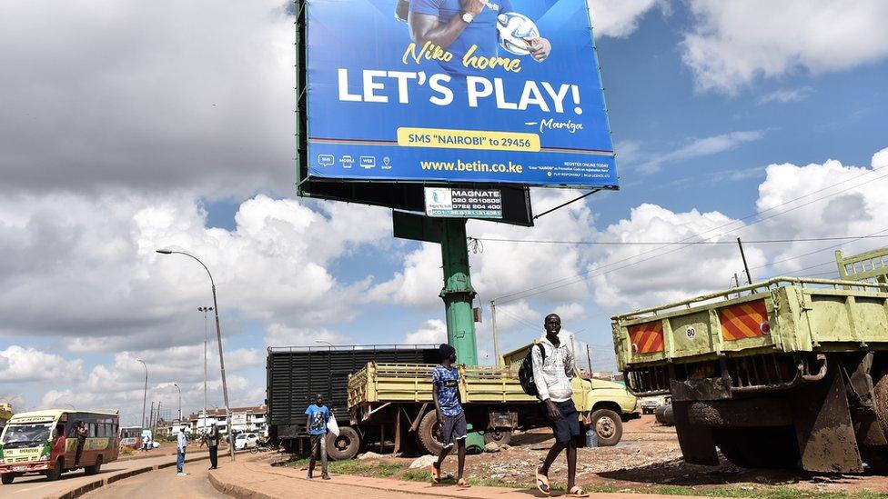 Boys walk under a billboard advertising a popular sports betting site in Nairobi's Kawangware suburb - November 2017