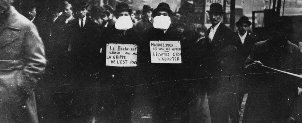 Dos hombres con máscaras para protegerse de la gripe en las calle de París.