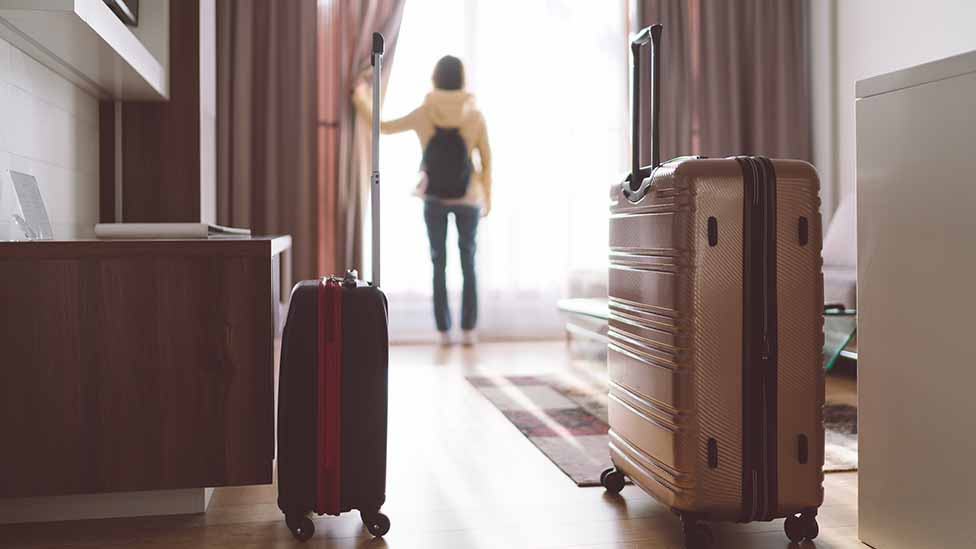 Woman with suitcases opens curtain in hotel room