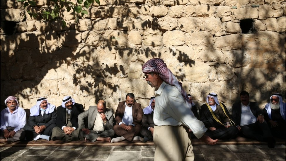Men sit against a wall in Lalish ahead of the inauguration ceremony for the new Yazidi spiritual leader