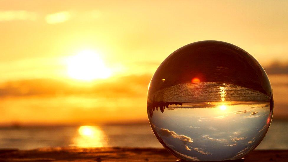 Bola de cristal por la que se refleja el atardecer.