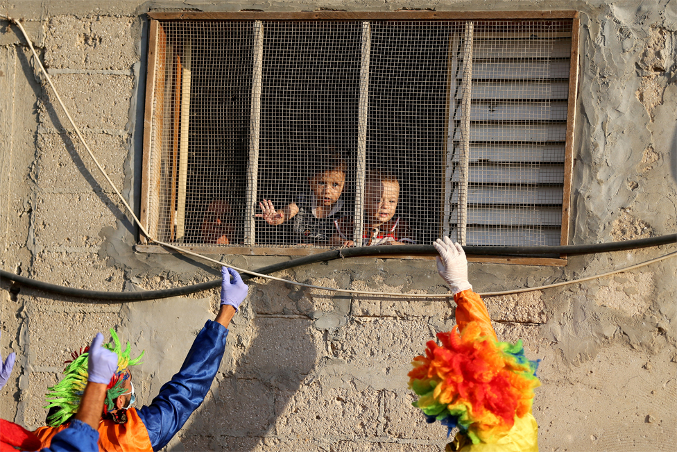 Clowns wave at children who look out of a window
