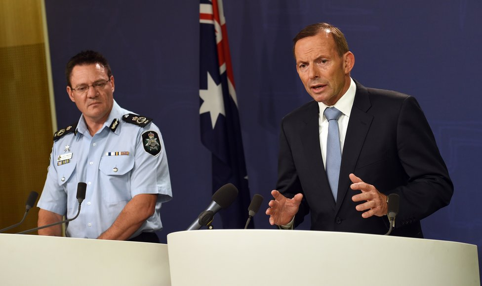 Australia's Prime Minister Tony Abbott (R) speaks to the media as Australian Federal Police deputy commissioner Michael Phelan (L) listens in Sydney on 18 April 2015, after two men were arrested in Melbourne for allegedly planning an Islamic State-inspired terrorist attack using 'edged knives' on a ceremony commemorating Anzac soldiers who have fought and died for their country