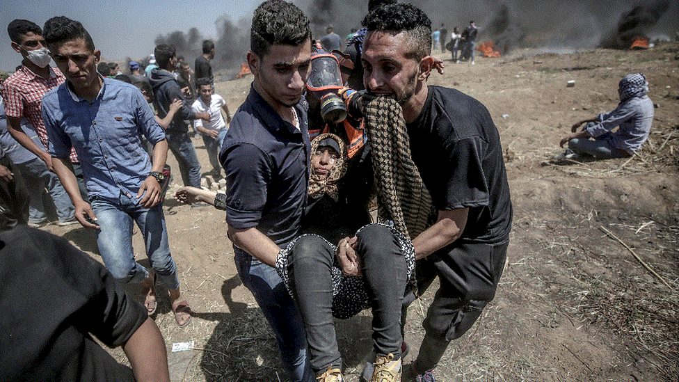 Palestinian protesters carry a wounded female protester during clashes after protests near the border with Israel in the east of Gaza Strip