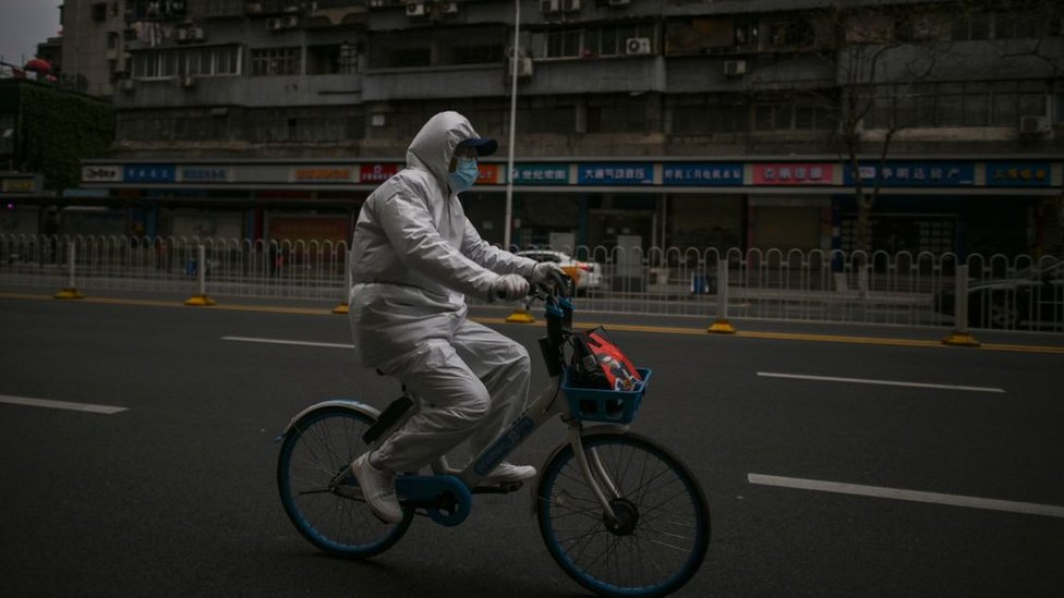 Un hombre vestido en traje protector monta una bicicleta en Wuhan