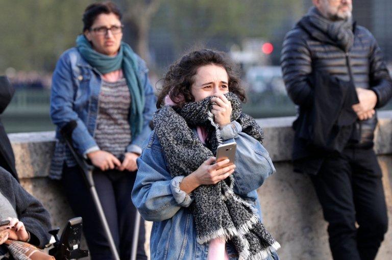 Seorang perempuan terisak menyaksikan Notre Dame terbakar di depan matanya