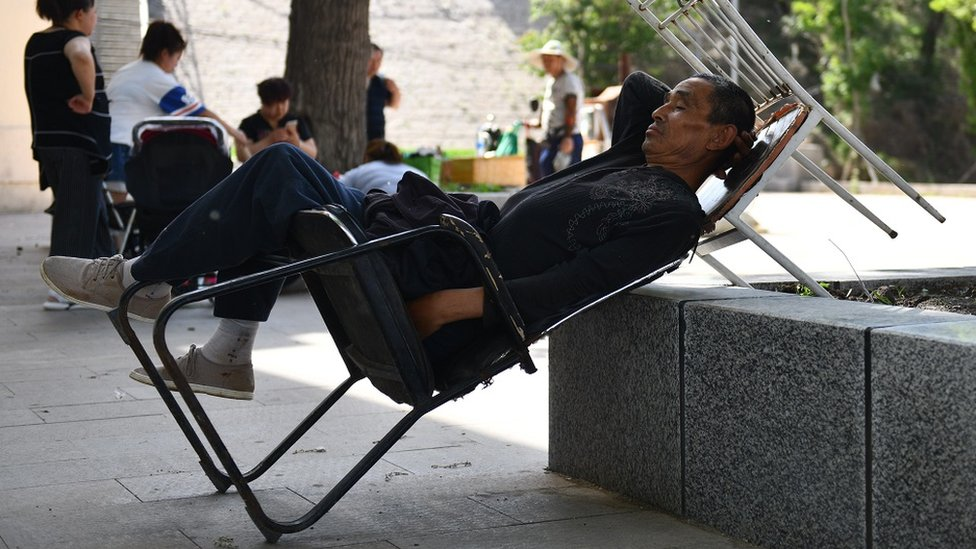 A Chinese man is having a nap on a chair, in a public square