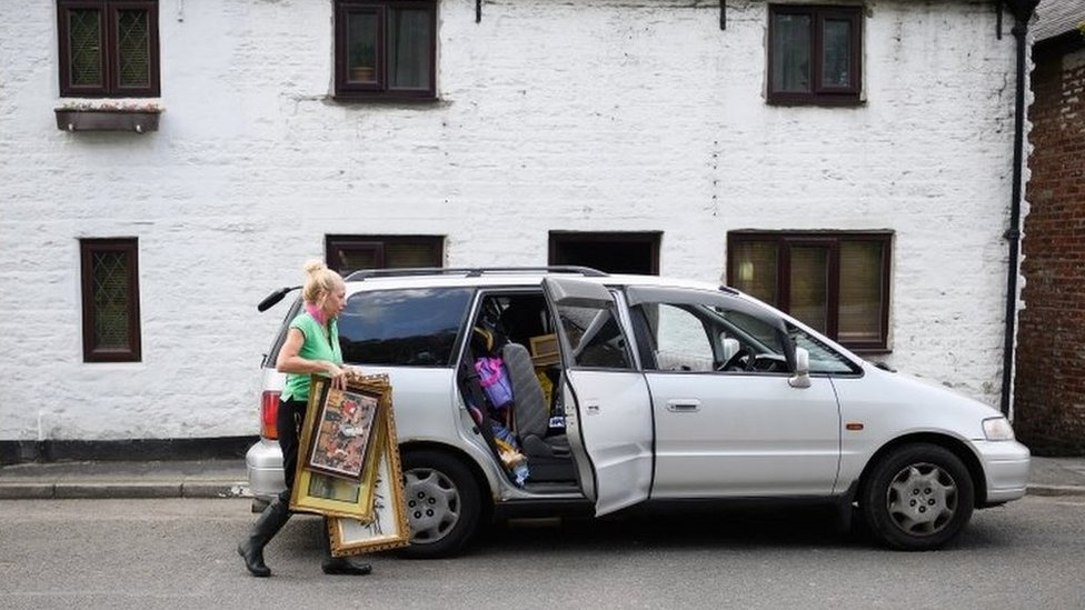 Woman packs paintings into car