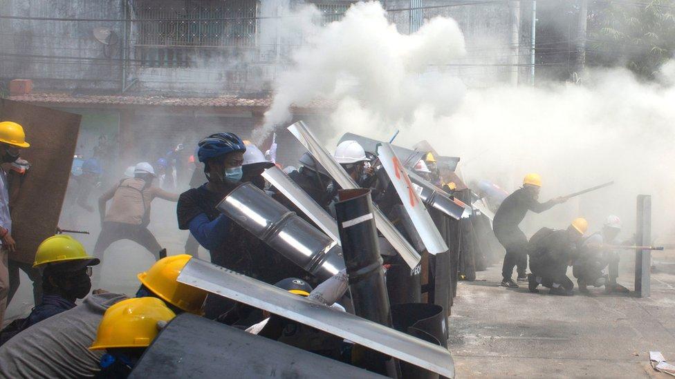 Manifestantes se protegen en las calles de Yangón.