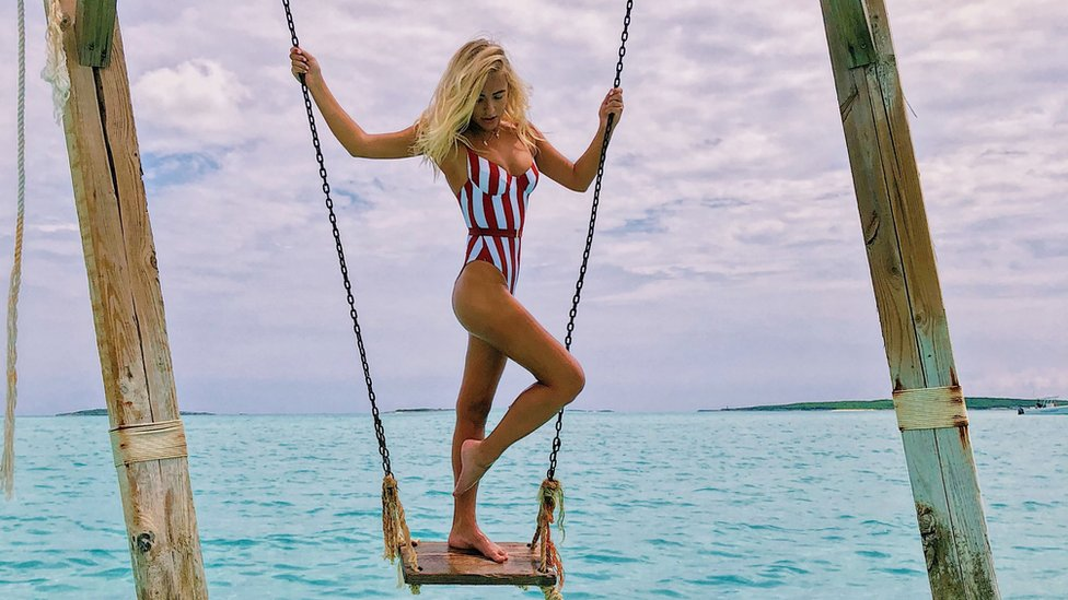 Katarina stands on a swing above the ocean