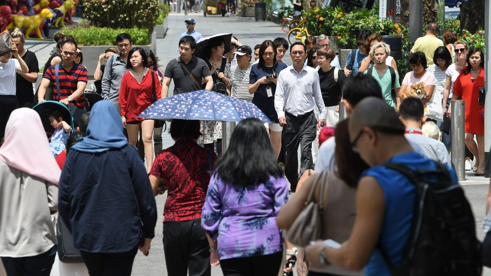 Pedestrians wait to cross the street along the Orchard Road shopping district in Singapore on February 21, 2018.