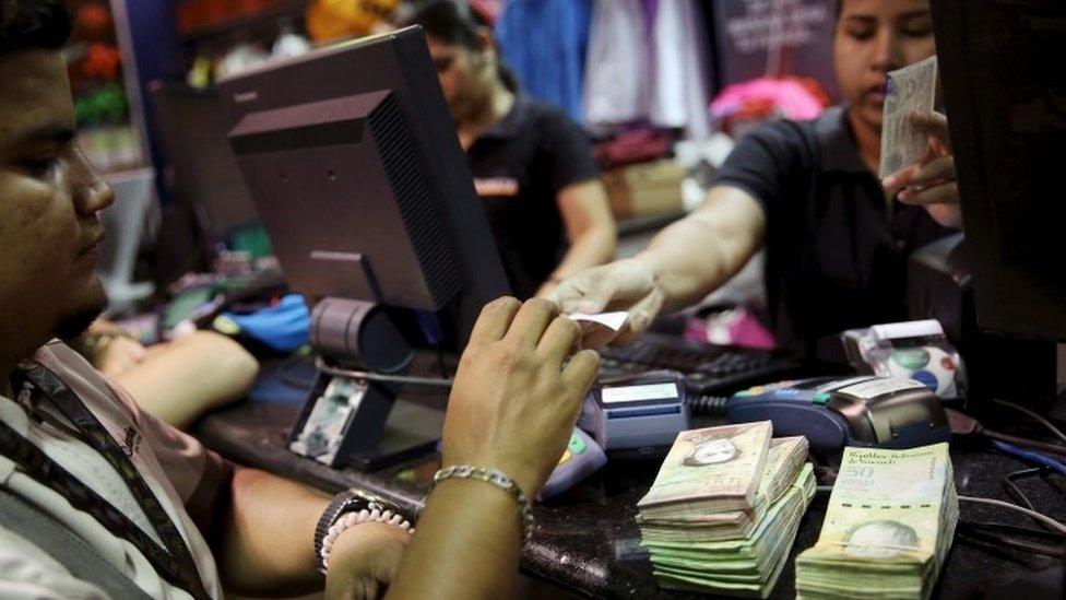 A customer pay a cashier in Venezuela, 9 Dec 2015