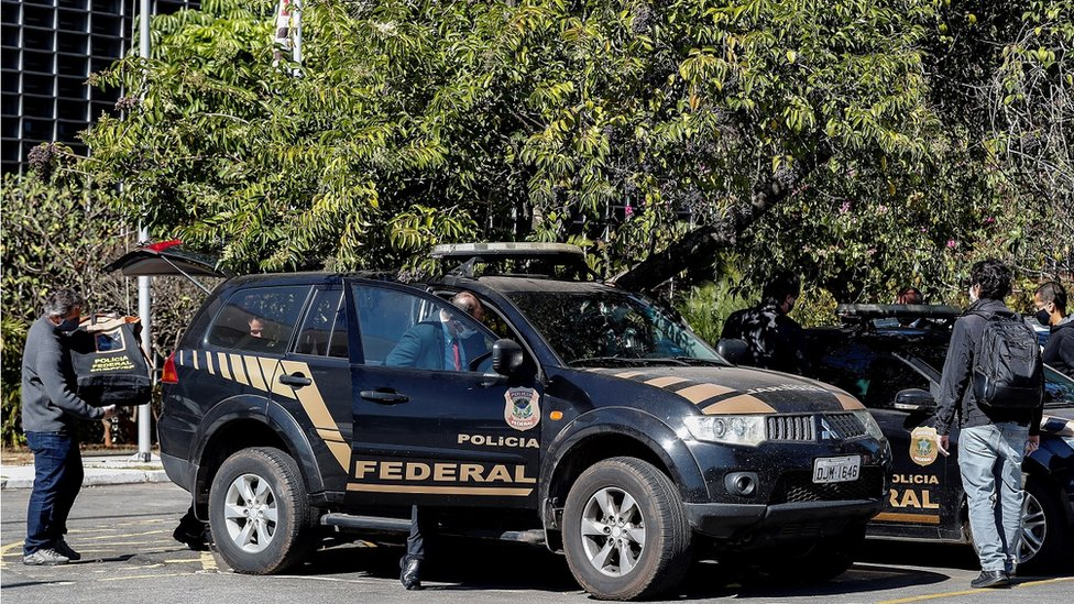 Carro da polícia federal e agentes
