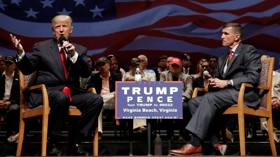 Donald Trump and General Flynn sit on stage in front of an audience during an election rally