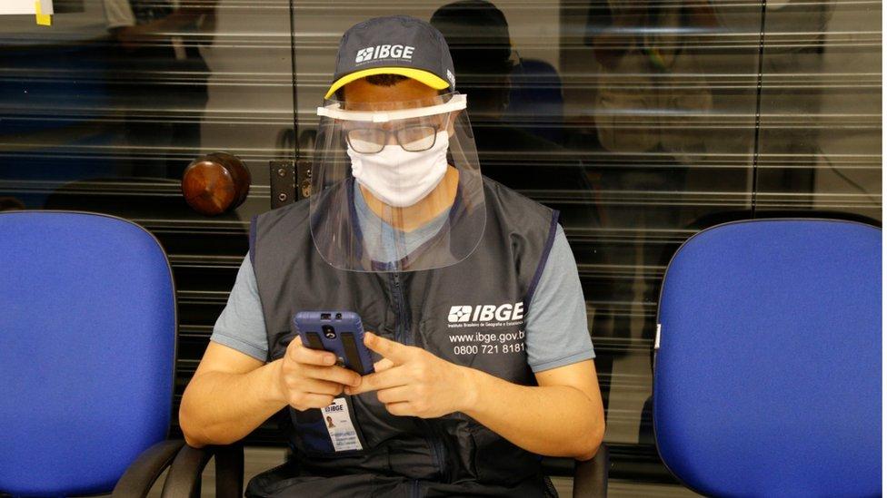 Agente do censo usando boné e colete do IBGE, além de máscara de proteção e face shield contra o coronavírus