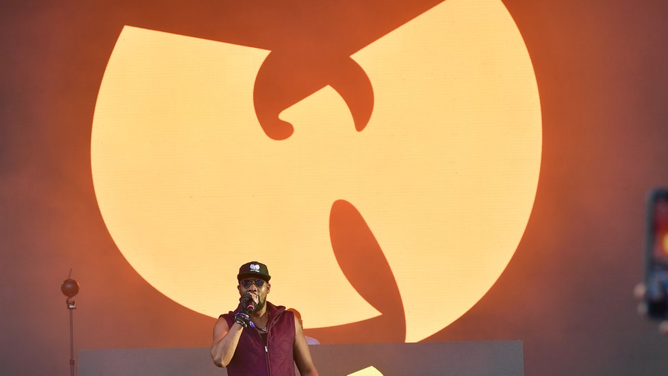 Picture of RZA in front of a Wu-Tang Clan symbol