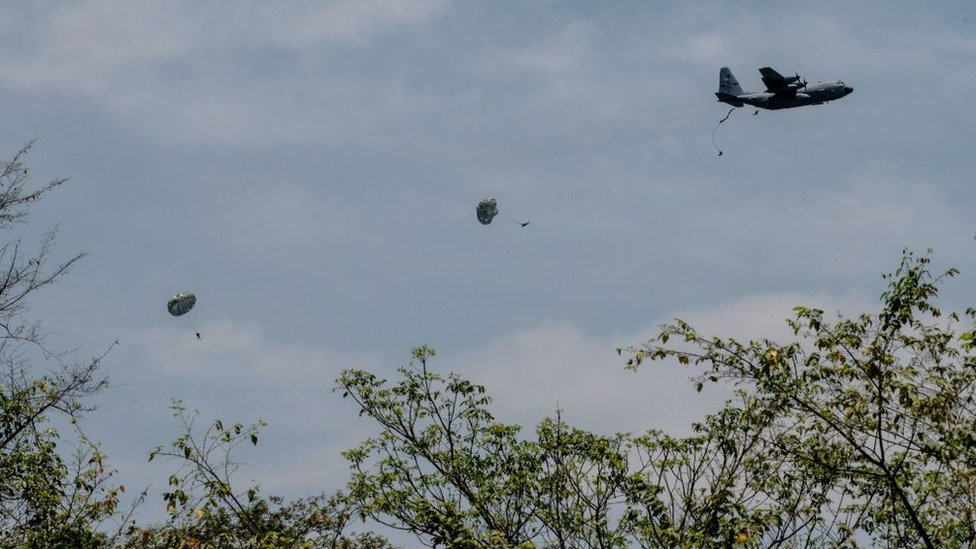 Avión y paracaidistas saltando