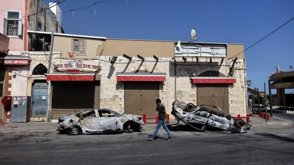 Un hombre camina, pasando dos vehiculos incendiados en la ciudad israelí de Lod.