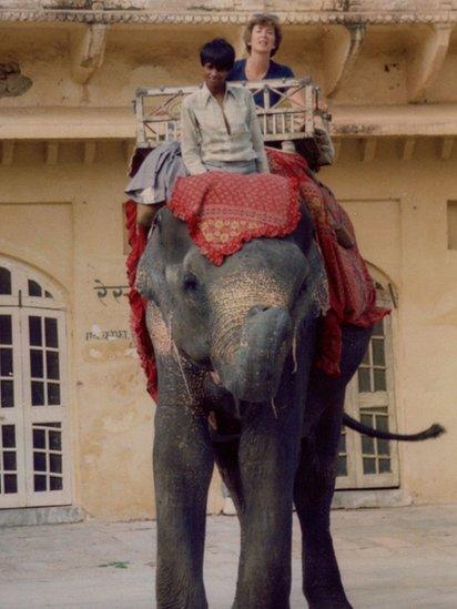 Jonna Mendez y un niño sentados en un elefante