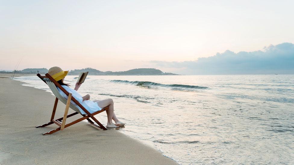 Mujer leyendo sentada frente al mar