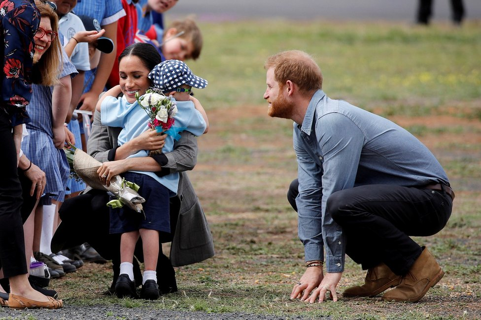 Prince Harry and Meghan, Duchess of Sussex, with a child at Dubbo airport, Dubbo, Australia, October 17, 2018