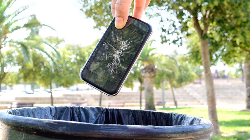 tirando un iphone a la basura