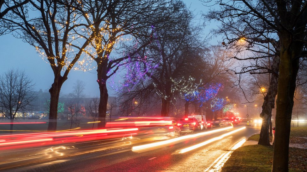 cars at dusk with christmas lights