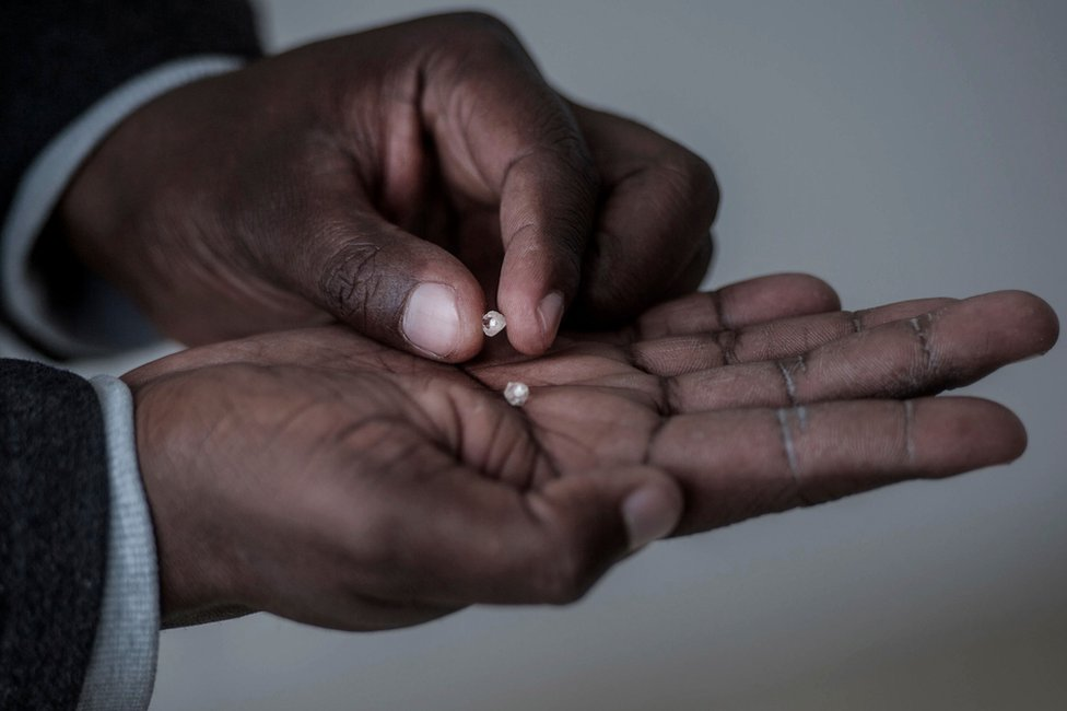 """A man holds rough diamonds found by former illegal, now independent, miners, on June 5, 2018 in Kimberly, Northern Cape, South Africa. Unlike formal mining operations, small-scale miners pan for precious minerals around the edge of established quarries in the hope of coming up lucky. In April, some 800 illicit miners received licences to operate on a vast tract of land near Kimberley in the country""""s centre. The landmark deal was aimed at curbing the rapid growth of illegal mining which has been spurred on by rising unemployment."""