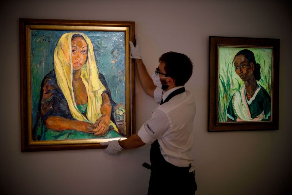 A gallery worker poses with an artwork entitled The Yellow Shawl (L) alongside The Green Sari (R) by South African artist Irma Stern.