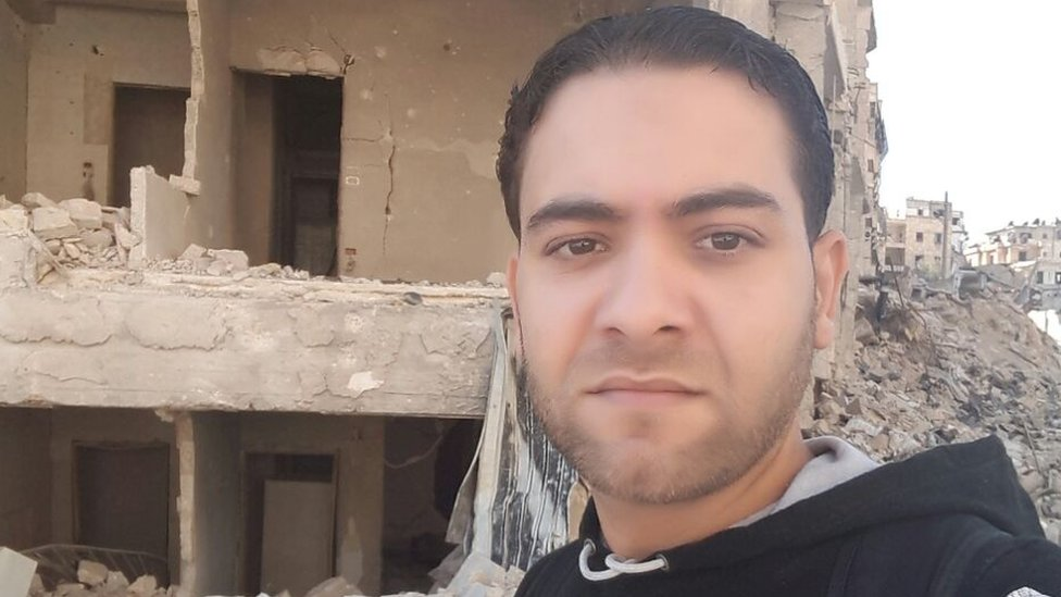 Mohammed in front of some ruined buildings in Aleppo