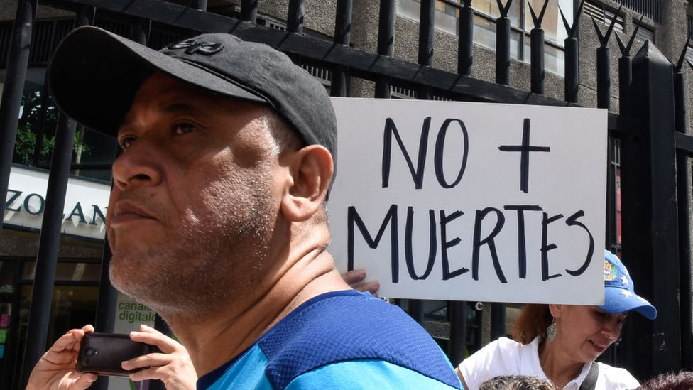"""Una persona con un cartel que dice """"No más muertes""""."""