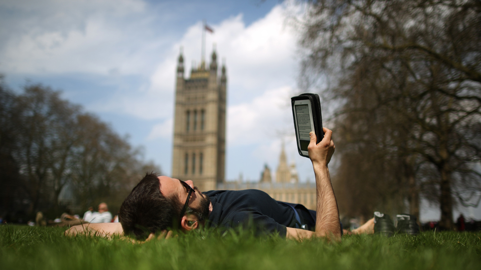 Man reads e-book on grass outside the Houses of Parliament