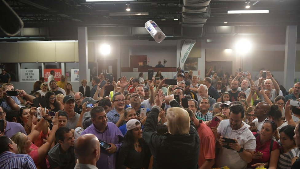 US President Donald Trump throws a paper towel roll as he visits the Cavalry Chapel in Guaynabo, Puerto Rico