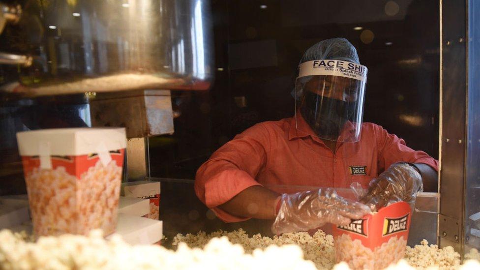 Seorang pekerja menyiapkan popcorn dengan langkah-langkah kesehatan dan keamanan setelah bioskop dibuka kembali di India