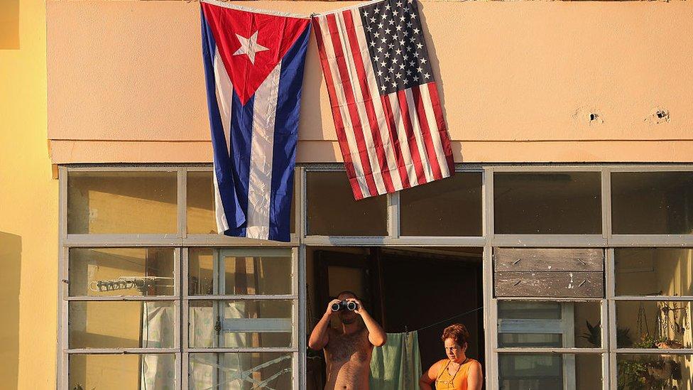 Ciudadanos cubanos observan desde una ventana la ceremonia de apertura de la embajada de EE.UU. en La Habana.