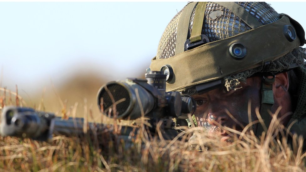 A British military sniper from the looks though his scope during the 16 Air Assault Brigade Exercise Joint Warrior at West Freugh Airfield
