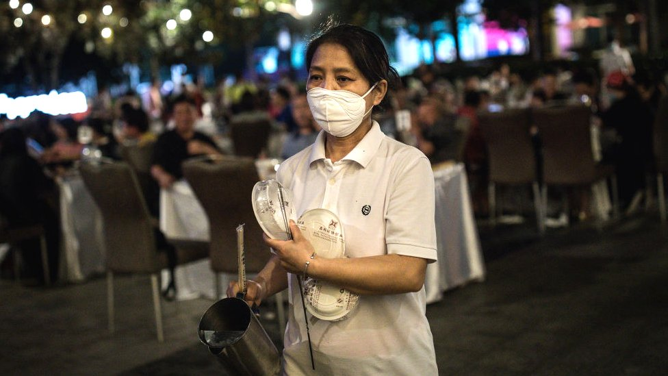 A waiter wears a protective mask while serving on the open platform of the Sheraton hotel on May 28.2020 in Wuhan, China.