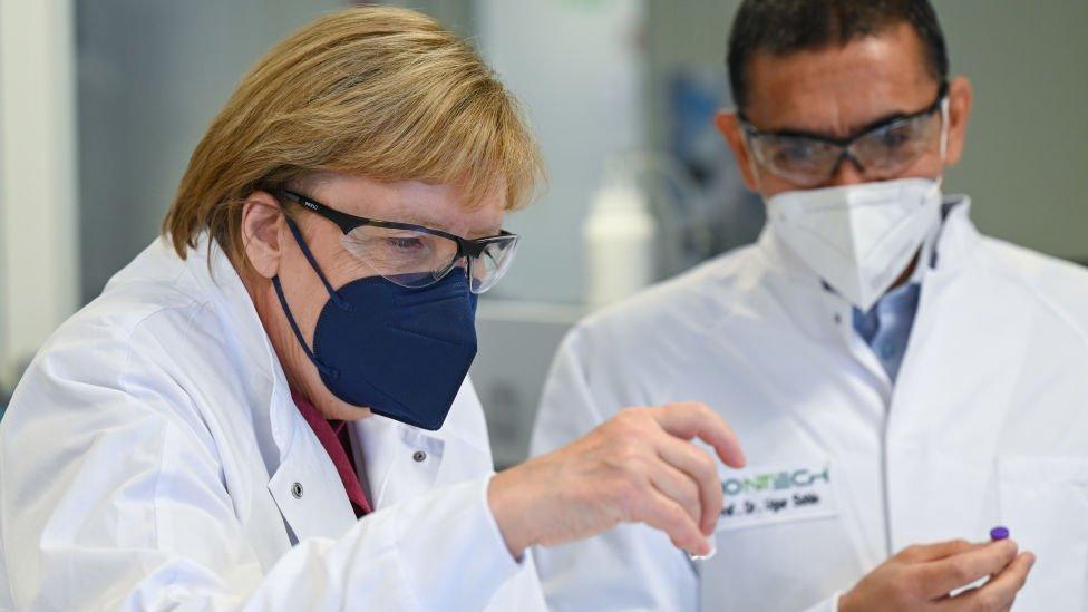 Ugur Sahin, osnivač i izvršni direktor biotehnološke kompanije BionTek pokazuje Angeli Merkle ampulu Fajzer vakcine u Marburgu