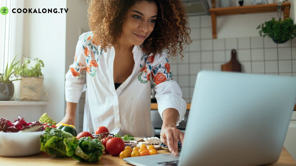 Woman cooking with laptop