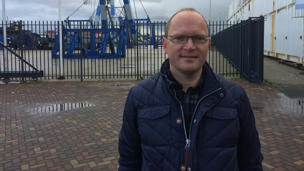 Peter Westdijk in front of cranes at the port of Rotterdam