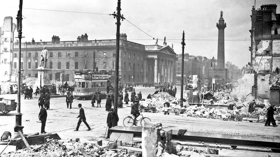 Crowds in Sackville Street (now O'Connell Street) can be seen next to the General Post Office showing damage from shelling following the Easter Uprising