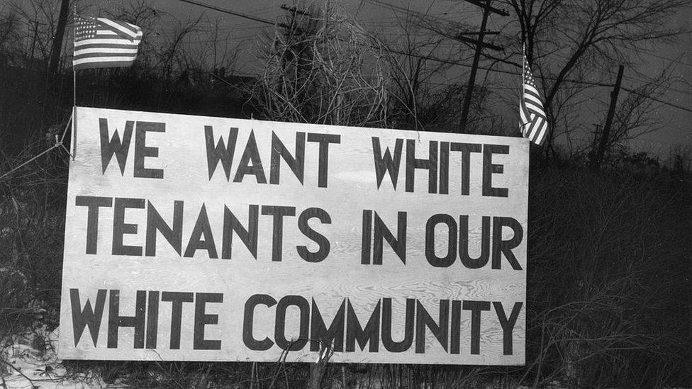 """Un aviso dispuesto en Detroit (Michigan) en 1942 frente a un proyecto de vivienda social que dice """"Queremos inquilinos blancos en nuestra comunidad blanca""""."""