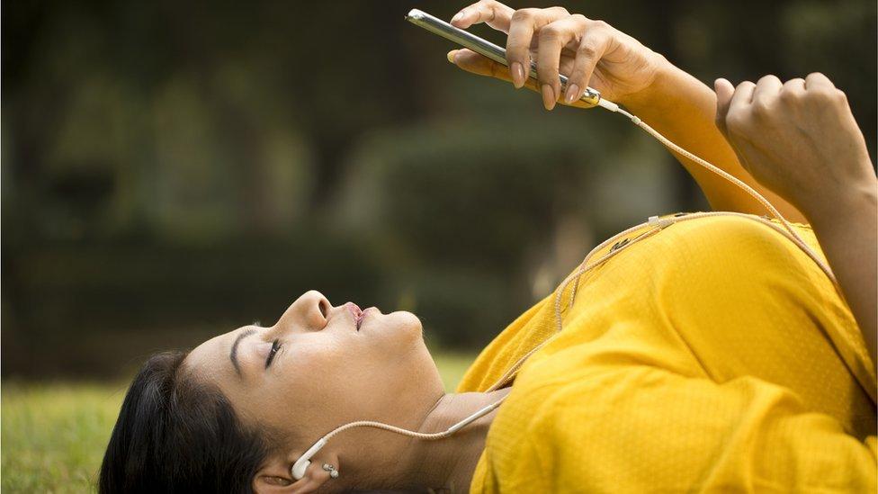 Una mujer recostada en el suelo con un celular.