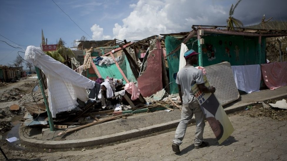 A man carries an election poster in Les Anglais, Haiti, 10 October 2016, in the aftermath of Hurricane Matthew