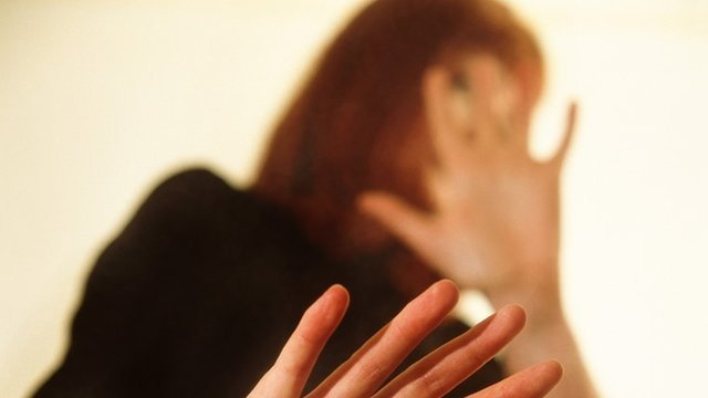 Woman shielding herself from violent partner